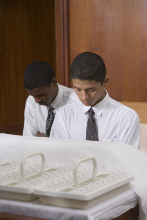 Two dark-haired young men in white shirts and ties bow their heads at the sacrament table to bless the sacrament.
