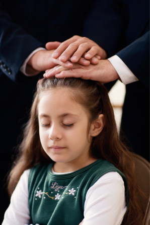 A girl with long brown hair bowing her head while two men in suits place their hands on her head to confirm her a member of the Church.