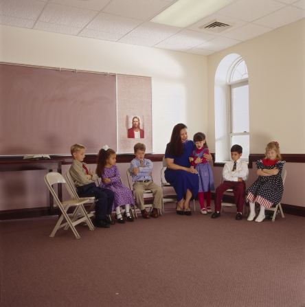 A girl praying in a Primary class, with five other classmates and one female teacher.