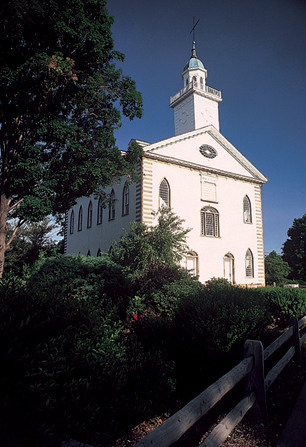 A view of the Kirtland Temple from the bottom of the hill, with a clear blue sky behind the spire.