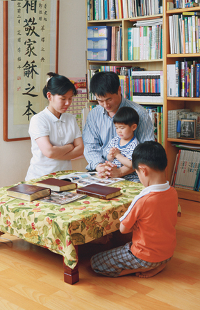 A photograph by Hyun-Gyu Lee of a family of four in Korea kneeling around a table for family prayer.