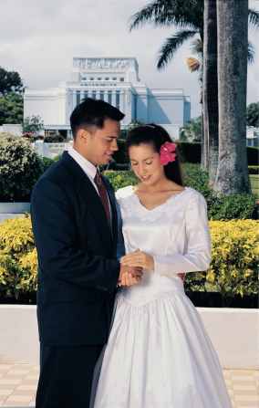 A man in a dark suit and a woman in a white wedding gown standing together in front of the Laie Hawaii Temple on their wedding day.