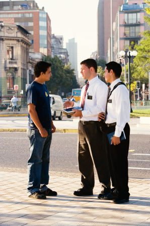 Two male missionaries in white shirts and ties standing on a busy street corner, talking to a young man in jeans and a T-shirt.