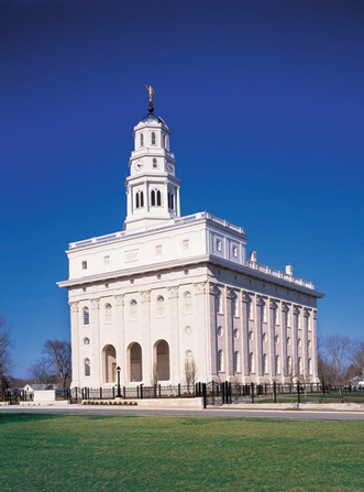 The Nauvoo Illinois Temple on a clear, sunny day, with green lawns and a black gate in the foreground.