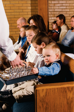 A blond toddler reaching out to take a cup of water from a sacrament tray being passed to him in a sacrament meeting.