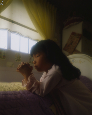 A young girl with black hair kneels at the side of her bed in the morning with her hands clasped and eyes closed in prayer.