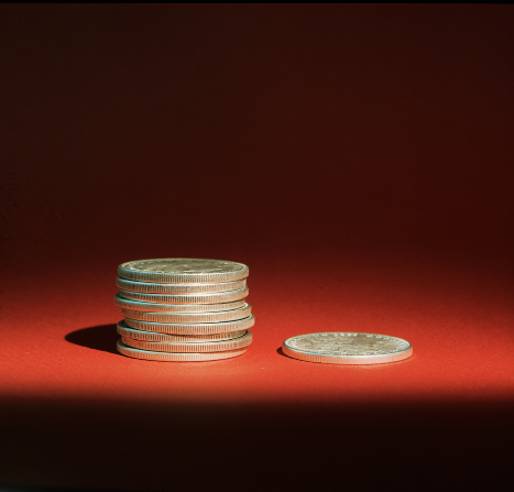 A stack of nine silver coins next to a single silver coin on a red background, with a single light source casting shadows.