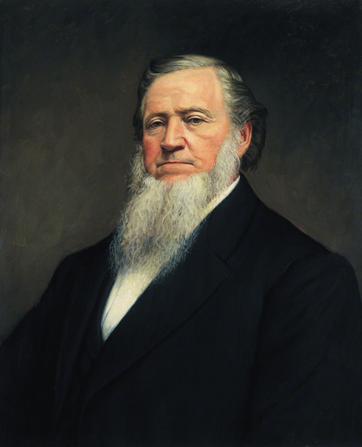 A painted portrait by John Willard Clawson of Brigham Young with a long white beard, wearing a black suit.