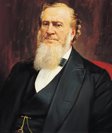 A painted portrait by John Mulvany of Brigham Young in a black suit, sitting in a red chair.