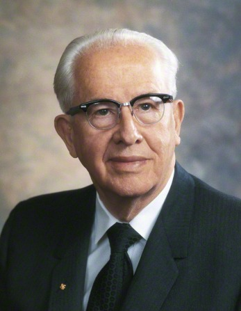 A portrait of President Ezra Taft Benson in a black suit, white shirt, and glasses.