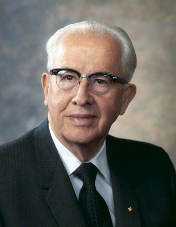 A portrait photograph of President Ezra Taft Benson in a pinstriped suit and glasses with dark rims.