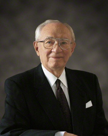 A portrait of President Gordon B. Hinckley smiling in a black suit, white shirt, and glasses.