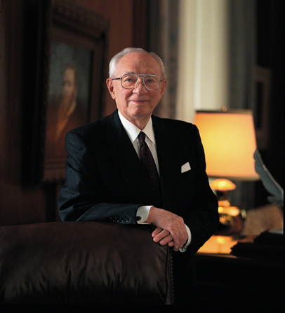 A portrait photograph by Jed A. Clark of Gordon B. Hinckley in a dark suit, standing with his arm resting on a leather chair.