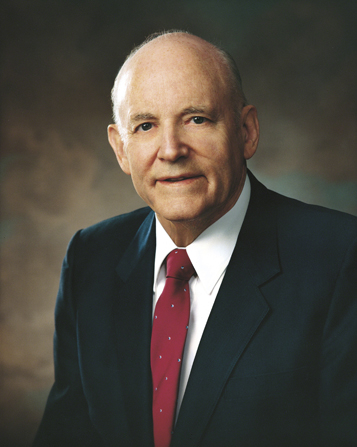 A portrait of President Howard W. Hunter in a dark blue suit, white shirt, and red tie.