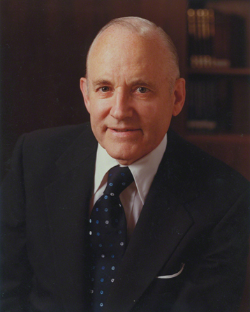 A portrait photograph by Busath Photography of Howard W. Hunter in a dark suit and blue tie.