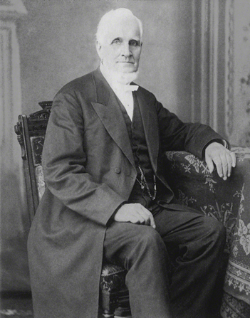 A black-and-white photograph of John Taylor sitting in a black suit and a long coat.