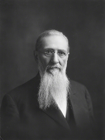 A black-and-white portrait photograph of Joseph F. Smith with a long white beard and small round glasses.