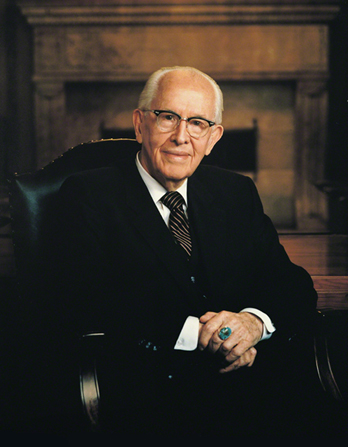 A portrait photograph by Busath Photography of Ezra Taft Benson in a dark suit and striped tie, sitting in a dark leather chair.