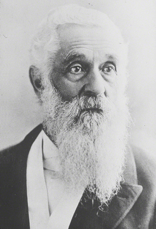 A portrait photograph by Charles Roscoe Savage of Lorenzo Snow in a dark suit.