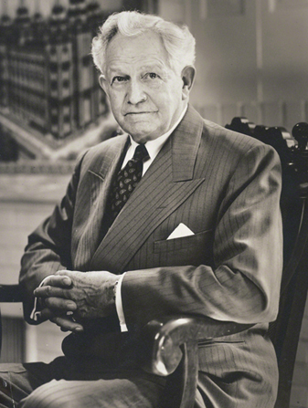 A portrait photograph of David O. McKay in a pinstriped suit, sitting in a wooden chair.