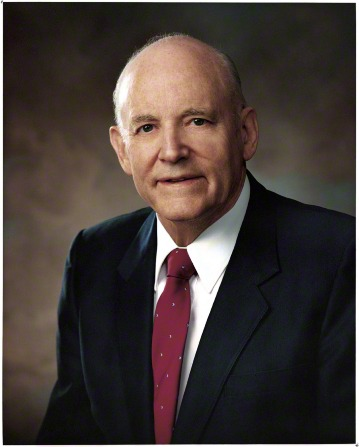 A portrait photograph of Howard W. Hunter in a dark suit and red tie against a gray background.