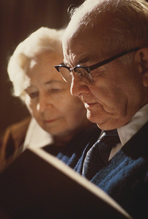 A photograph by Eldon Keith Linschoten of President Spencer W. Kimball and his wife, Camilla Kimball, looking at a book together.