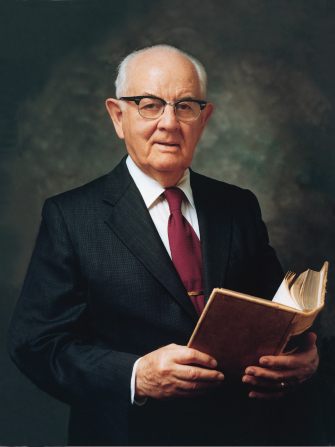 A portrait of President Spencer W. Kimball wearing a white shirt, red tie, and black suit, holding a book.