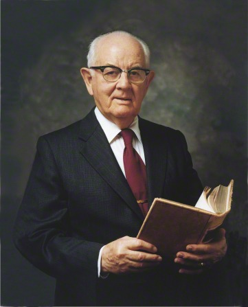 A painted portrait of President Spencer W. Kimball in a black suit, white shirt, and red tie, holding an open book.