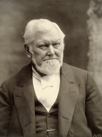 A black-and-white portrait photograph of Wilford Woodruff in a dark suit and white shirt.