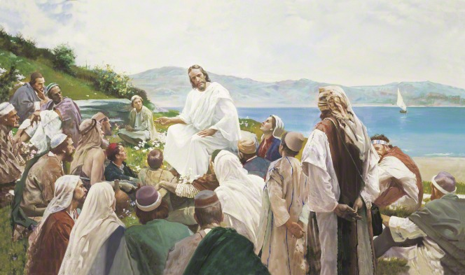 Jesus in white robes, sitting on a hillside by the sea, surrounded by a large group of people who are listening to His teachings.