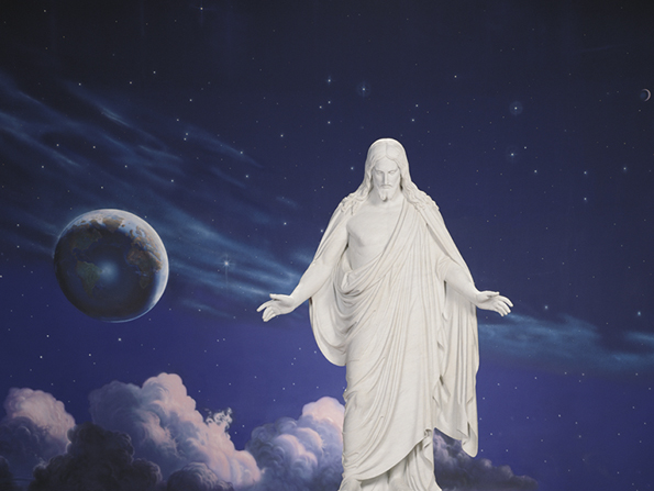 A white statue of the Savior standing in front of a deep blue and purple depiction of the heavens painted on the wall.