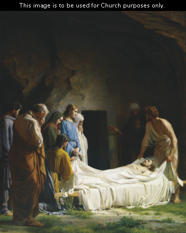 Christ's friends wrapping His body in white linens to prepare Him to be placed into a tomb, which is seen in the background.
