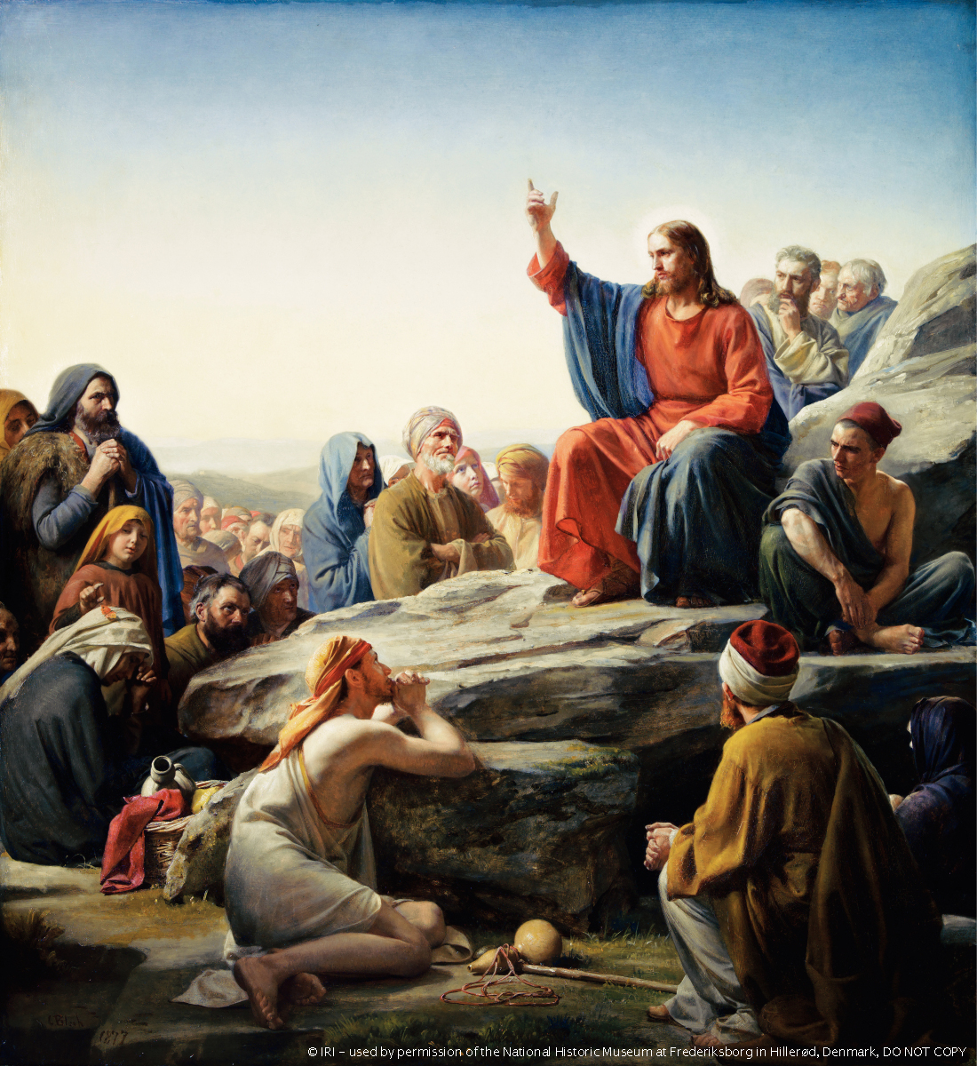 Christ in red and blue robes, sitting on a large rock and teaching, while a large group of people sit around Him listening to His words.
