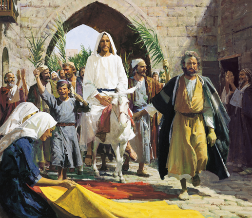 Christ in a white robe, riding a white donkey through a stone archway while a crowd waves palm fronds and lays red and yellow cloths in His path.