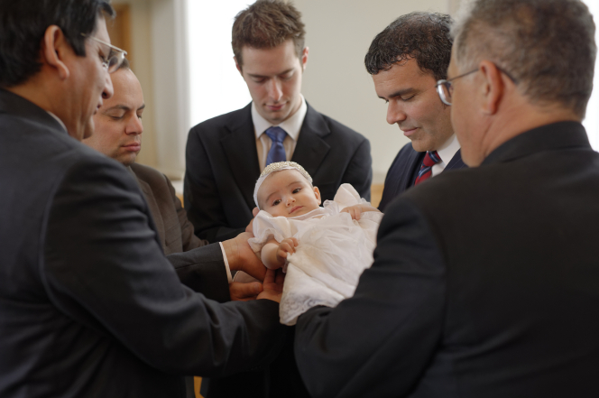 A group of men in suits holding and blessing an infant.