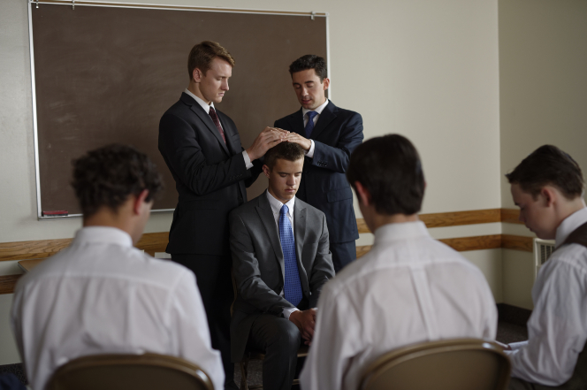 Two men ordaining another in a meetinghouse classroom.