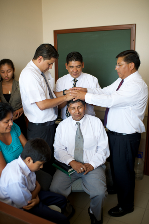 Three men giving another man a blessing in Bolivia.