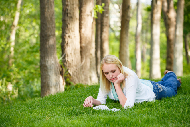 A young woman lying on the grass and reading the Book of Mormon.