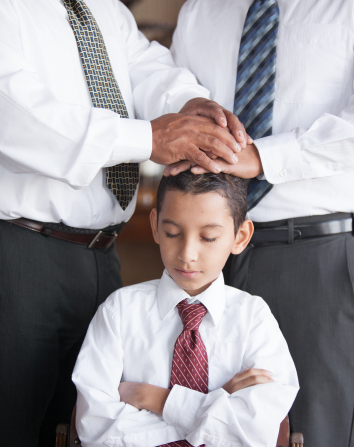 A young boy in a white shirt and tie being confirmed by two men.