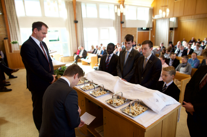 A young man in Norway kneeling and blessing the sacrament.