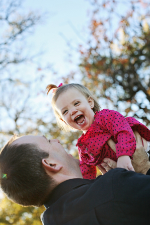 A father holds his baby girl up in the air while she laughs.