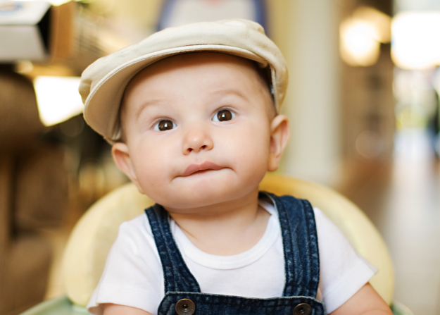 A baby boy in overalls and a hat, sitting and looking up.