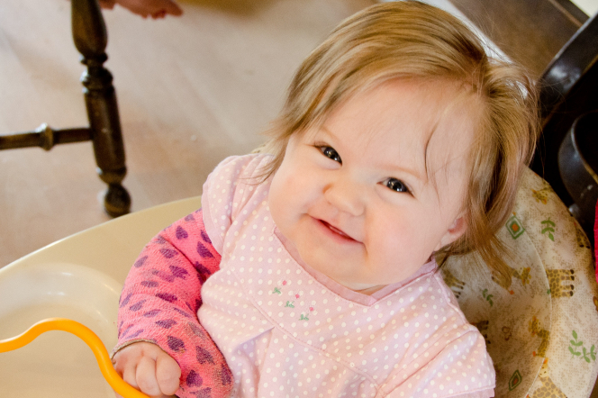 A baby girl sitting in a high chair, looking up and smiling.