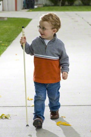 A young boy wearing glasses and using a white cane for the blind as he walks down a sidewalk.