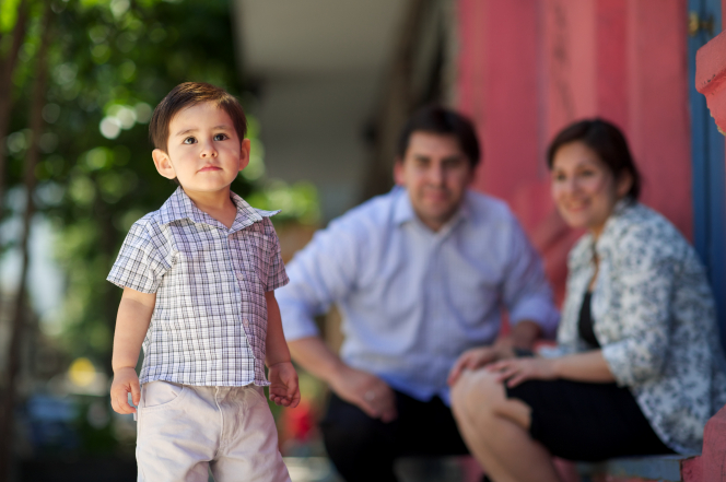 A toddler boy walking forward with his parents sitting down behind him.