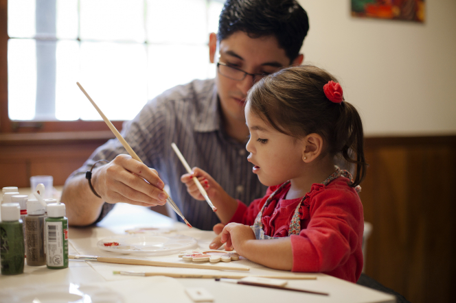 A father in glasses and a plaid shirt sitting beside his young daughter in a red shirt at a table, each holding a paintbrush.