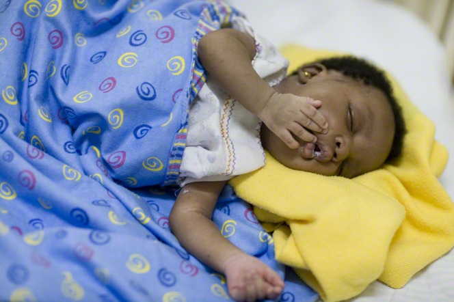 A newborn from Ghana lies sleeping with her hand on her face.