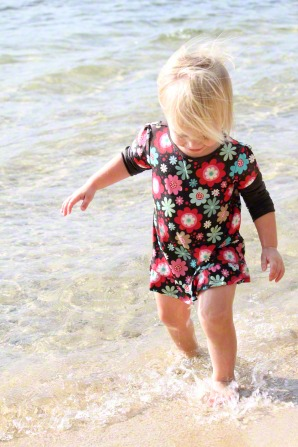 A little girl in a flowered dress walks in water along the shore.