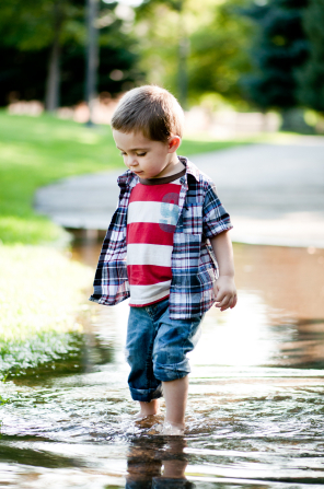 A toddler boy with rolled-up pants walks outside in a deep puddle of water.