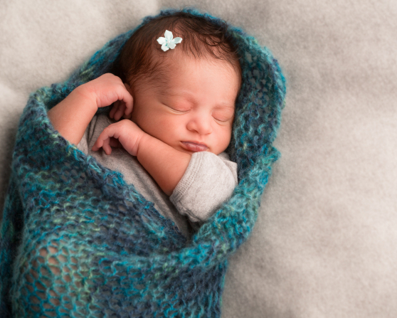 A newborn baby girl asleep, wrapped in a blue knit blanket.